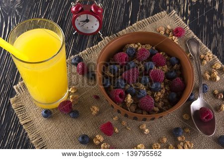 Muesli with fresh berries orange juice and alarm clock on wooden background.