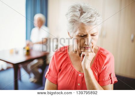 Thoughtful senior woman touching her chin in a retirement home