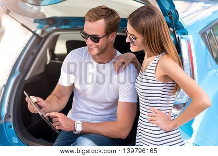 So useful device. Young modern couple sitting on the trunk of the electric car and looking at the tablet