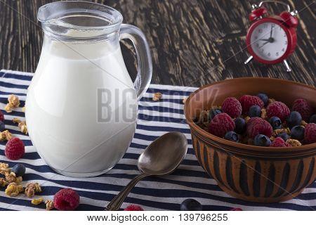 Muesli with fresh berries milk and alarm clock on wooden background.