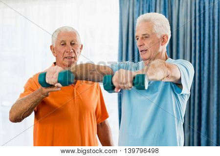 Senior exercising with weights in a studio