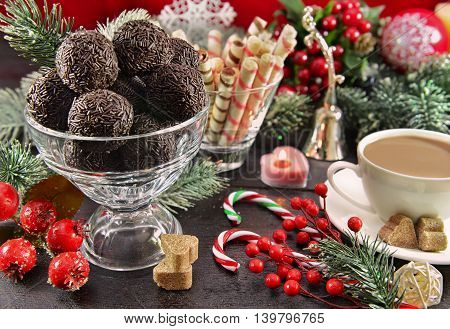 Sweet chocolate dessert on festive table with decorations and cup of cocoa. Christmas and New Year celebratory food still life