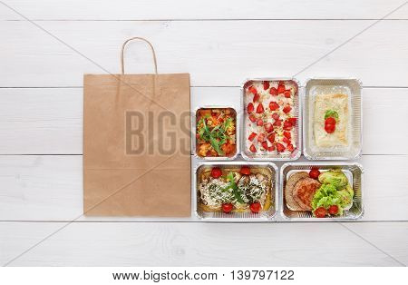 Healthy food delivery, daily meals and snacks. Diet nutrition, vegetables, meat and fruits in foil boxes and brown paper bag package. Top view, flat lay at white wood with copy space