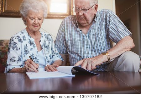 Senior Husband And Wife Doing Paperwork Together At Home