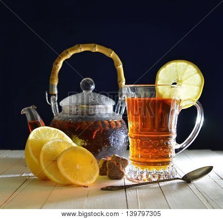Tea still life with fresh tea in glass kitchenware, sliced lemons, brown sugar and spoon on dark blue background