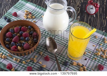 Muesli with fresh berries, orange juice, milk and alarm clock on wooden background.