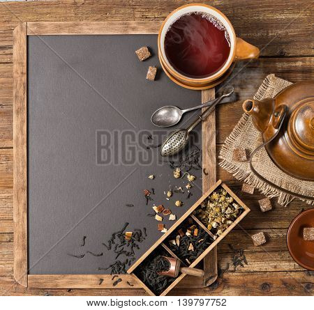 Top view of tea ceremony: teapot tea cup and various kinds of tea on a blackboard. Free space for menu .