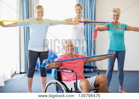 instructor and seniors exercising with stretching bands during sports class