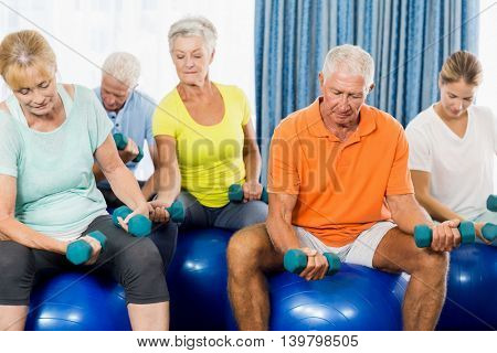 Seniors using exercise ball and weights during sports class