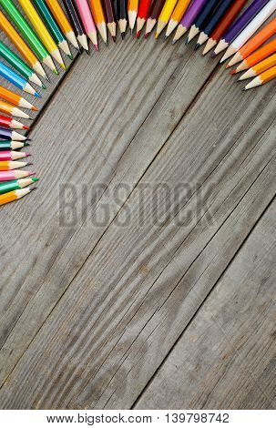 Colored pencils on wooden background with copy space top view. Colored pencils background
