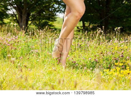 girl standing barefoot on the grass on sunny summer day. legs closeup