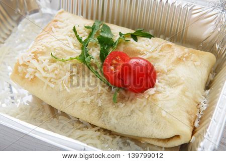 Healthy food delivery and diet concept. Take away of fitness meal. Weight loss nutrition in foil boxes. Flatbread roll with vegetables, cherry tomato and arugula at white wood