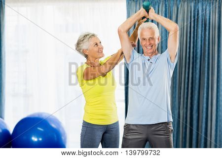 Senior man using weights in a sport studio
