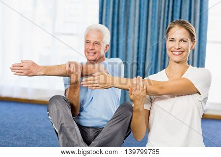 Instructor helping senior man with sport exercises during sports class