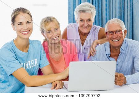 Volunteer and seniors using a laptop in a retirement home