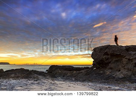 Silhouette of person standing on a rock at Currumbin rock Gold Coast, admiring the cloudscape at sunrise.