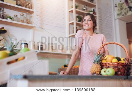 Portrait of young woman working at a juice bar standing at the counter. Juice bar owner looking away and smiling.