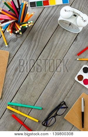 School different supplies on gray wooden table with copy space. Top view