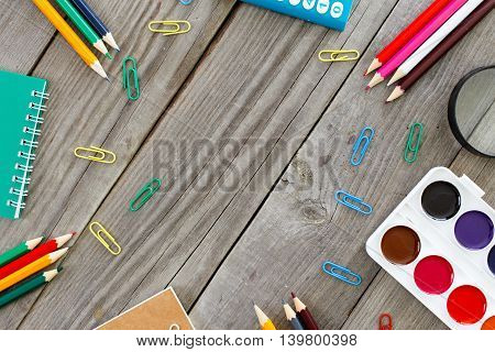 Desk with school supplies on wooden background. Top view