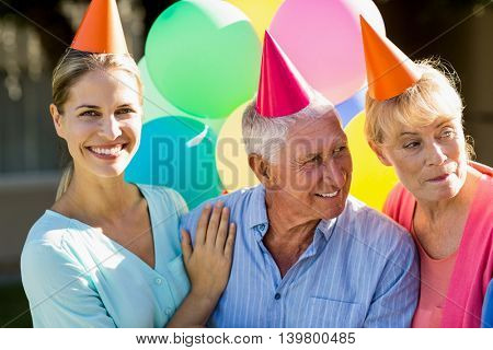 Nurse and seniors celebrating outside the retirement home