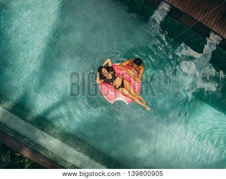 Couple Enjoying Vacation In Resort Pool