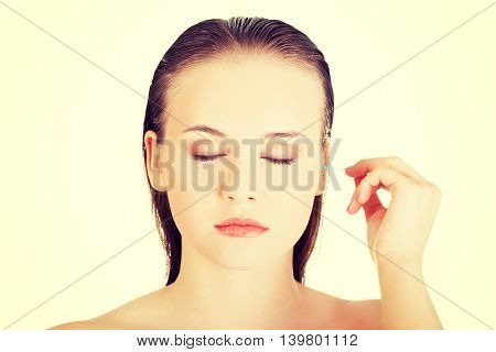 Woman face closeup while cleaning up an ear with a swab