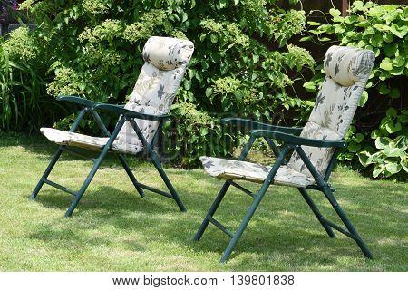 Garden chairs in the garden in sunshine