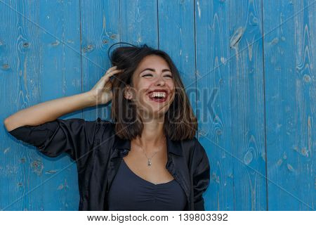 Young sexy suntanned woman in a short top and shirt with beautiful modern make-up and hair posing against blue painted wooden wall portrait with copy space horizontal view