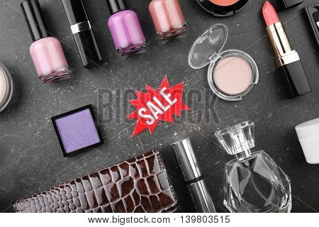 Sale concept. Bright tag with female stuff and cosmetics  on grey background