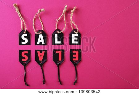 Paper tags with strings and word sale on pink background