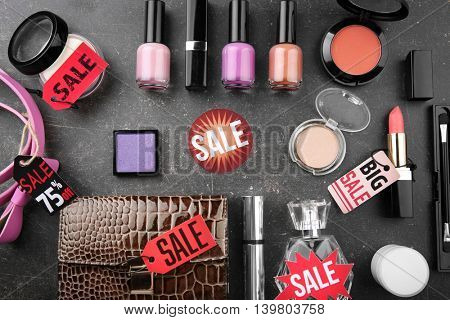 Sale concept. Bright tags with female stuff and cosmetics  on grey background