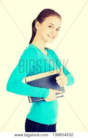 Student woman with book gesturing OK