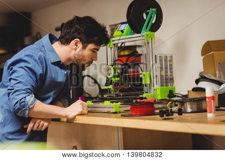 Graphic designer looking at machine in office