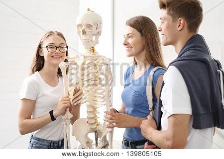 School, anatomy lesson, students watch a model skeleton