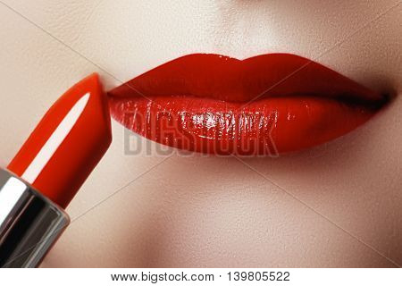 Extreme Close Up On Model Applying Red Lipstick. Makeup. Profess