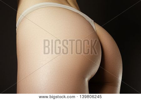 Beautiful Suntanned Female Buttocks Are Isolated On A White Back