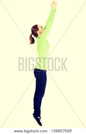 Attractive young woman jumping. Side view.