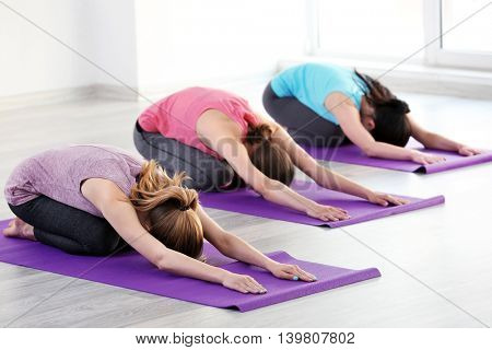 Young women doing yoga in gym