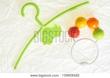 colored hanger, coat rack for infants clothing and a colorful rattle toy