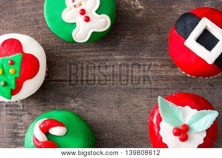 Sweet christmas cupcakes on rustic wooden table