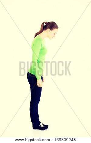 Woman standing and looking down.