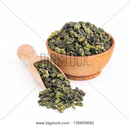 Tieguanyin oolong green tea in a wooden bowl isolated on white background