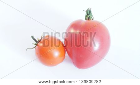 Tomato in the form Serce and round tomatoes lying on a white background