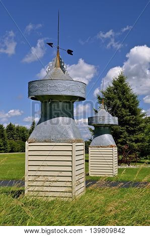 Two metal barn cupolas attached to bases are being used as decorations to the entrance of a roadway.