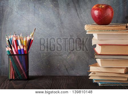 Books and supplies in front of classroom chalk board. Back to school concept with copy space