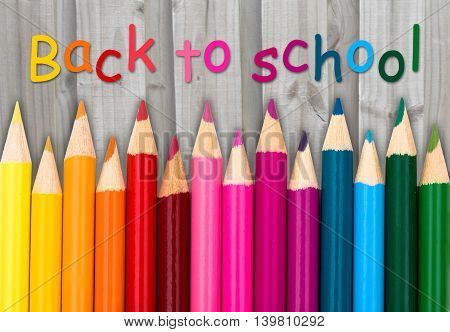 Pencil Crayons with text Back to School with weathered wood background