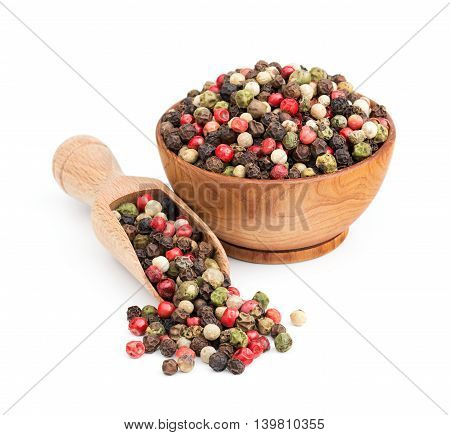 peppercorn mix in a wooden bowl isolated on white background