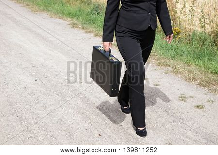 Woman on the dirt road with black briefcase