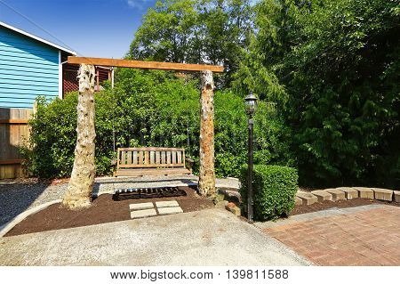 Wooden Swing Bench Outside In The Back Yard.