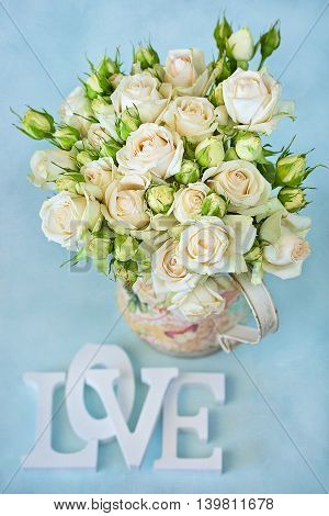 Roses flowers in a vase and letters